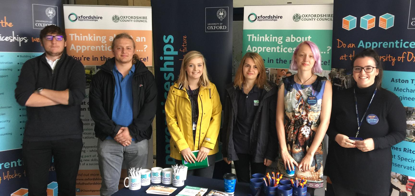 A mixed group of University of Oxford Apprentices at a careers fair talking about Oxfordshire Apprenticeships