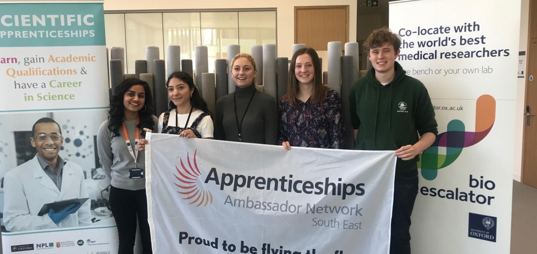 University laboratory technician apprentices holding the Apprenticeship ambassador flag during National Apprenticeship Week 2019