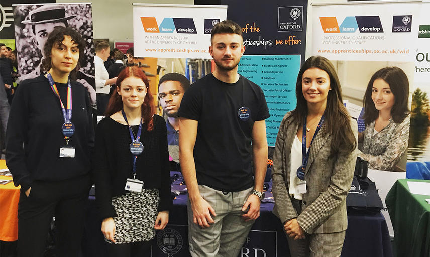 Four University apprentices next to our University Apprenticeships stand at the 2019 Career fest at BMW